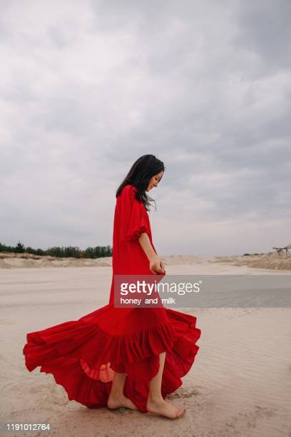 woman in a red dress standing in the desert, russia - red dress stock pictures, royalty-free photos & images