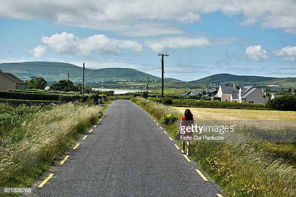 A woman in a red dress walking on roadside of Waterville in Ireland