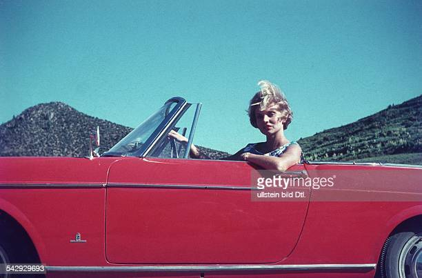 Woman in a red Fiat 1500 Spider with the logo of the Italian car design firm Pininfarina around 1960