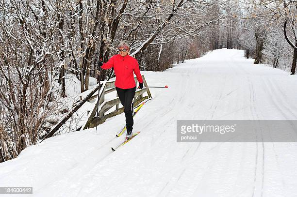 A woman in a red jacket cross-country skiing