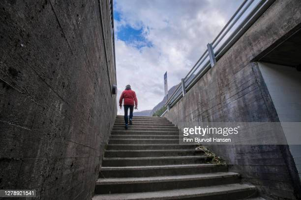 woman in a red jacket walking up stairs from a tunnel - finn bjurvoll stock pictures, royalty-free photos & images