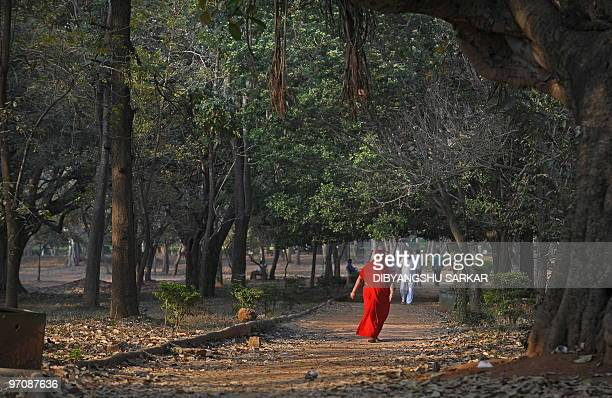 A woman in a red sari joins other morning walkers for a stroll in Cubbon Park in Bangalore on February 26 2010 The centrally located 300 acre park is...