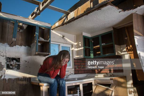 woman in a ruined home. - natural disaster stock pictures, royalty-free photos & images