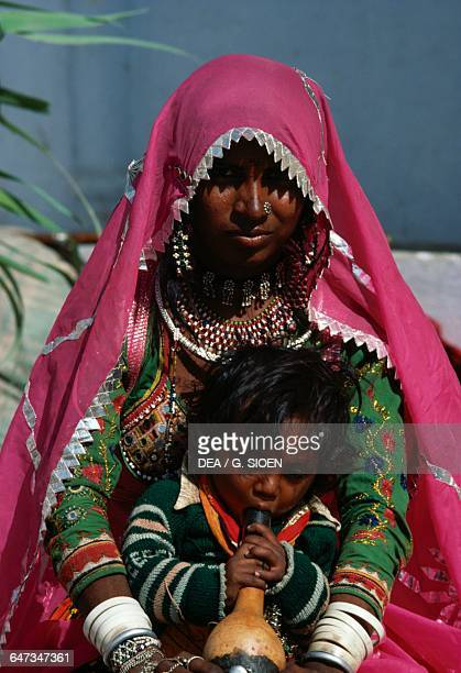 Woman in a sari wearing traditional clothes with a baby in her arms Rajasthan India