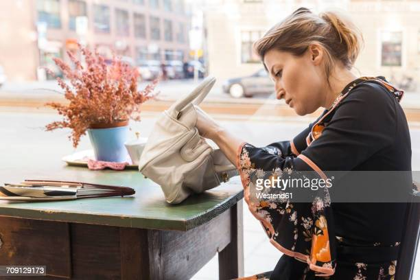 woman in a second hand shop looking for something in her handbag - handbag stock pictures, royalty-free photos & images