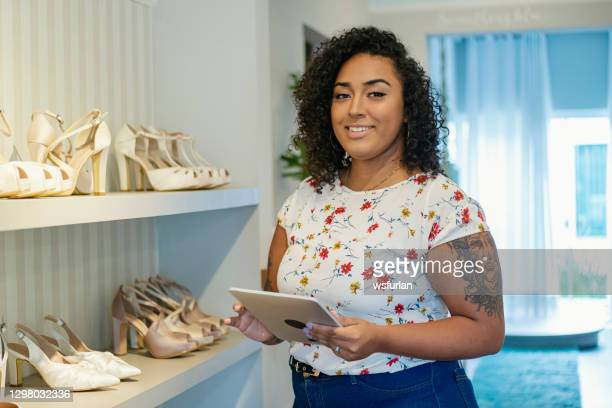 a woman in a shoes store - black shoe stock pictures, royalty-free photos & images