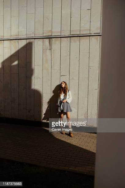 a woman in a short skirt is standing near the wall - legs and short skirt sitting down stock pictures, royalty-free photos & images