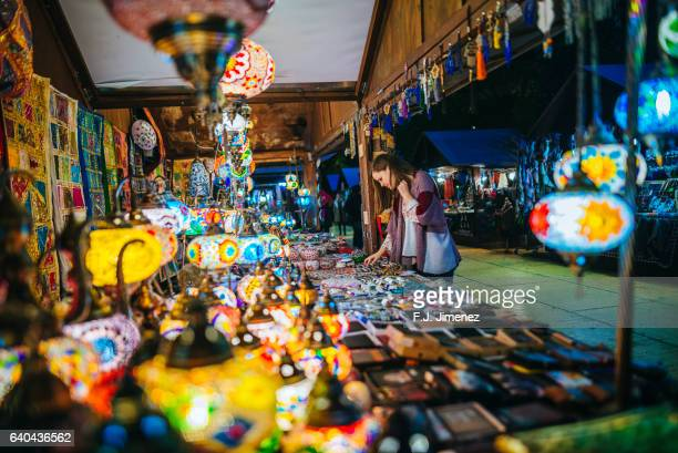 Woman in a street shop with colorful lamps