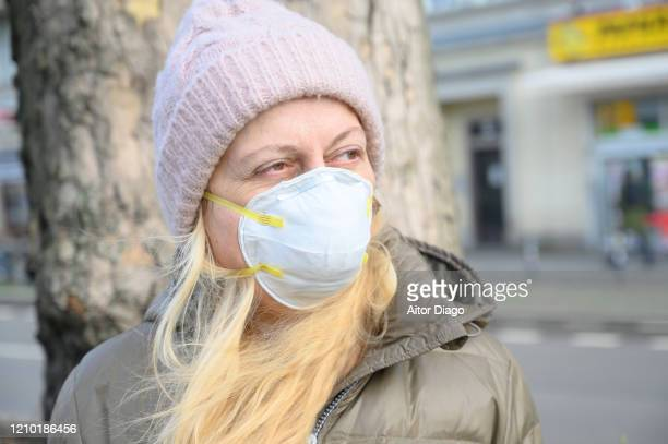 woman in a street wearing a protection mask close to a tree. berlin, germany. - 1918 flu pandemic stock pictures, royalty-free photos & images