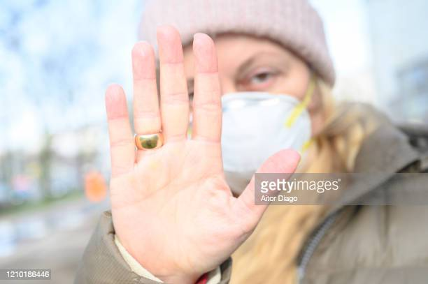 woman in a street wearing a protection mask doing stop sign with her hand. unrecognizable persons walking in a street in berlin, germany. - violence stock pictures, royalty-free photos & images
