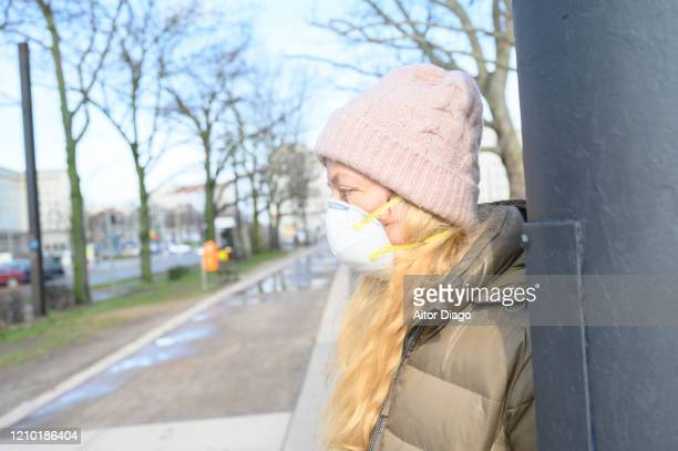 woman in a street wearing a protection mask resting on a metal column.  germany. - 1918 flu pandemic stock pictures, royalty-free photos & images