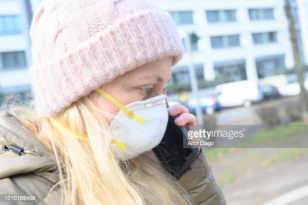 woman in a street wearing a protection mask talking with mobile phone. berlin, germany. - 1918 flu pandemic stock pictures, royalty-free photos & images
