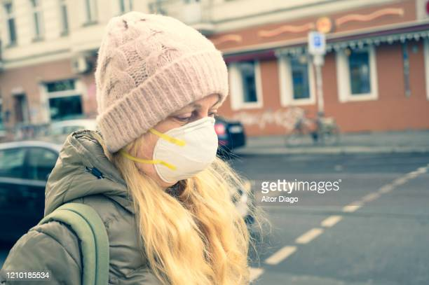woman in a street wearing a protection mask to avoid virus transmission. berlin, germany. - 1918 flu pandemic stock pictures, royalty-free photos & images