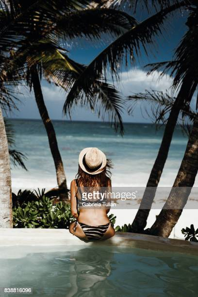 woman in a swimming pool in front of the beach - tulum mexico stock photos and pictures