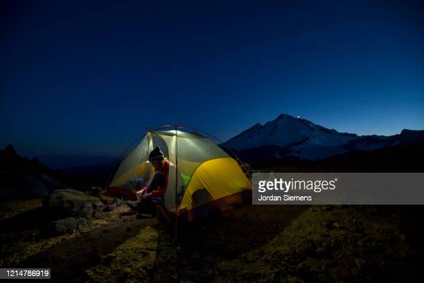 a woman in a tent while on a backpacking trip in the mt baker wilderness. - bellingham stock pictures, royalty-free photos & images