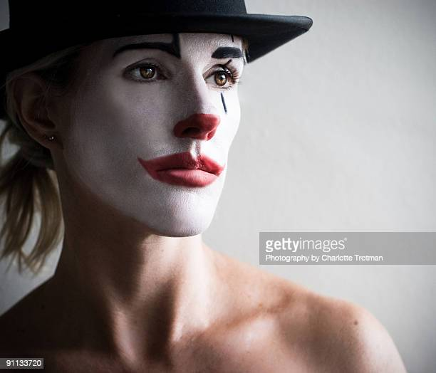 Woman in a top hat face painted as a pierot clown