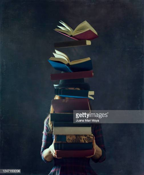 a woman in a top hat holds a large stack of books.  they cover her face and the books begin to fly. concept of wisdom, reading, culture, learning ... - literatur stock-fotos und bilder