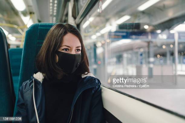 woman in a train wearing a face mask - london england stock pictures, royalty-free photos & images