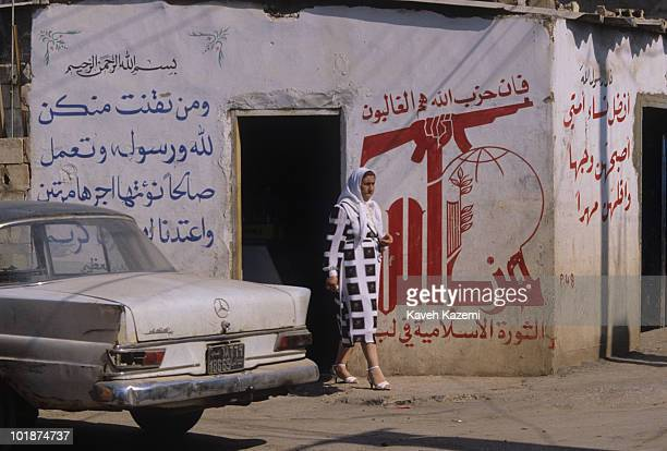 A woman in a veil walks past an old 1960s Mercedes Benz parked in front of a Hezbollah mural in southern suburb of Beirut during the civil war 12th...