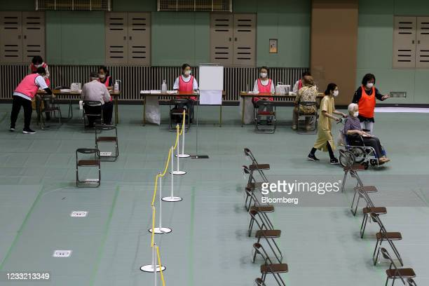 Woman in a wheelchair arrives to receive a dose of the Pfizer-BioNTech Covid-19 vaccine at an inoculation site at Miyakojima Sports Center in Osaka,...