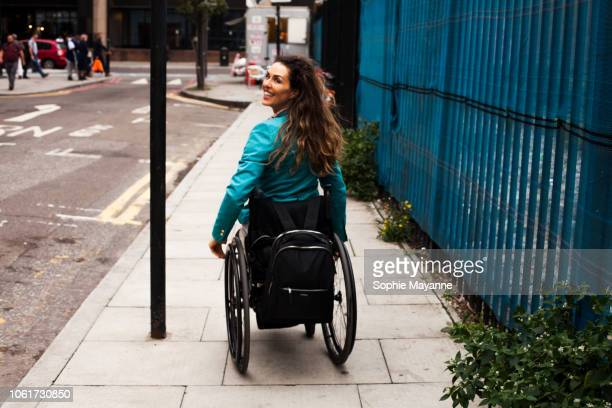 a woman in a wheelchair in the street looking over her shoulder - disabilitycollection foto e immagini stock