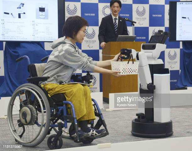 A woman in a wheelchair is handed a drink in a basket by a robot during an event in Tokyo on March 15 sponsored by the organizing committee for the...