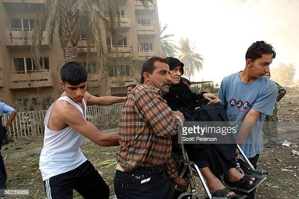 Woman in a wheelchair is taken to safety, as Iraqis cope with the aftermath of a double suicide car bomb attack that struck civilians living near the...