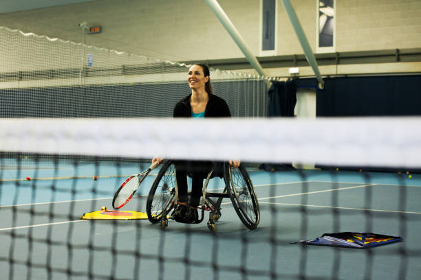 A woman in a wheelchair playing tennis
