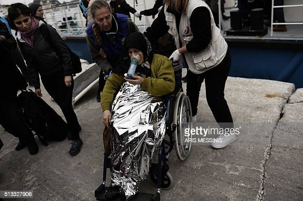 Woman in a wheelchair receives assistance as migrants and refugees arrive on the Greek island of Lesbos while crossing the Aegean Sea from Turkey on...