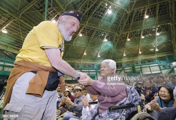 A woman in a wheelchair shakes hands with a retired US serviceman during a protest in Nago Japan on Dec 15 against US military aircraft Earlier in...