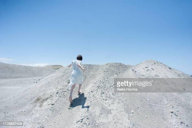 woman in a white dress climbing the dunes - 白のドレス ストックフォトと画像