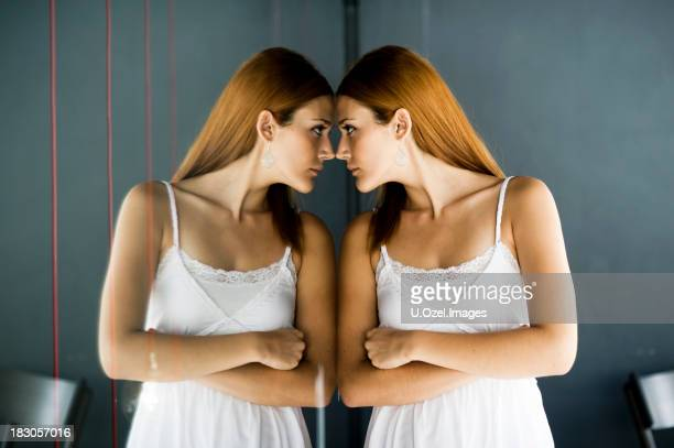 Woman in a white dress staring at her own reflection