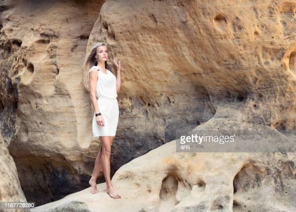 砂岩の洞窟で裸足で歩く白いドレスの女性 - 白のドレス ストックフォトと画像