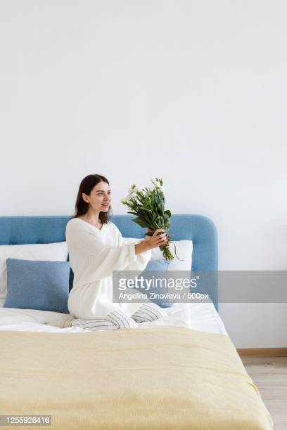 a woman in a white sweater sits on a bed holding a bouquet of white roses in her hand - angelina valentine stock pictures, royalty-free photos & images