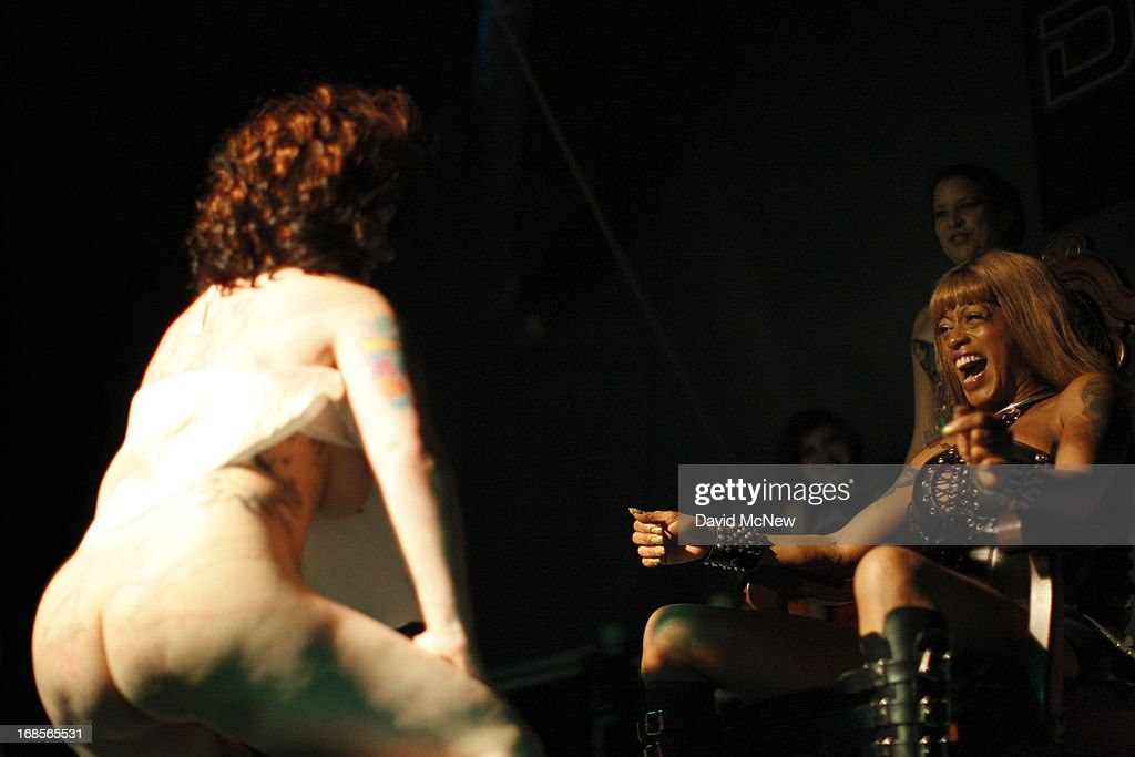 A woman in a wig dances for a dominatrix as men and women compete in a contest to be the best submissive at a dungeon party during the domination convention, DomConLA, in the early morning hours of May 11, 2013 in Los Angeles, California. The annual convention was started in 2003 by fetish professional Mistress Cyan to bring together enthusiasts of BDSM (Bondage, Discipline, Dominance/Submission, and Sadomasochism) and other fetishes.