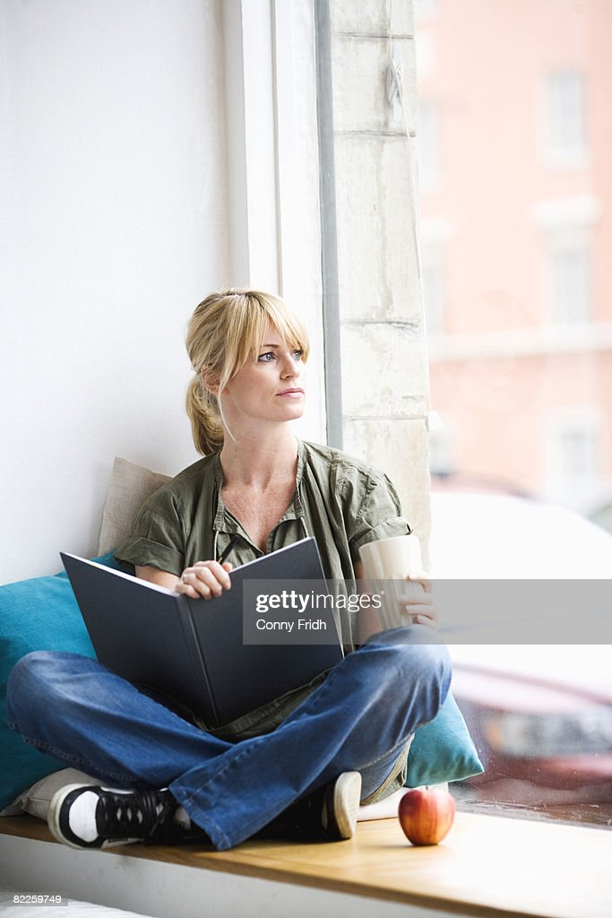 A woman in a window recess Sweden. : Stock Photo