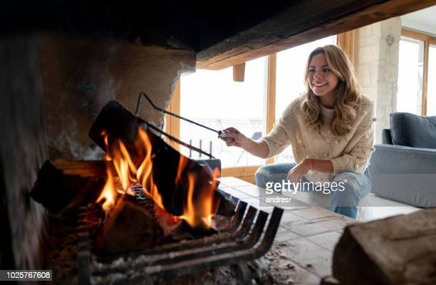 Woman in a winter lodge burning logs and looking happy