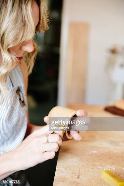 A woman in a workshop using a slab of wax to oil a small wood turned cup or bowl.