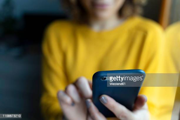 woman in a yellow pullover, using smartphone - woman texting stockfoto's en -beelden