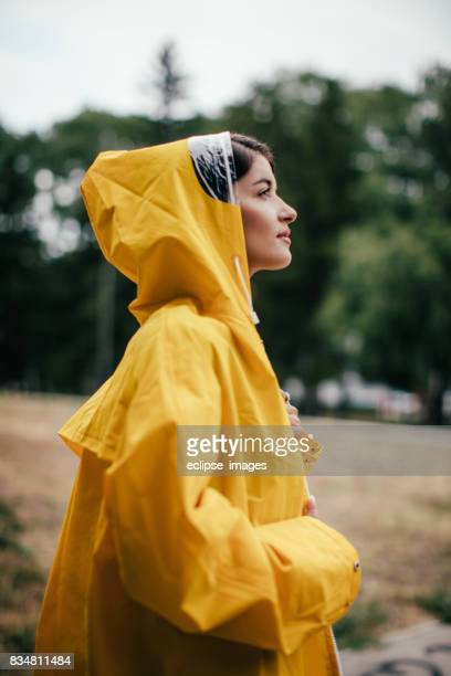 a woman in a yellow rain poncho enjoying the weather - gray jacket stock pictures, royalty-free photos & images