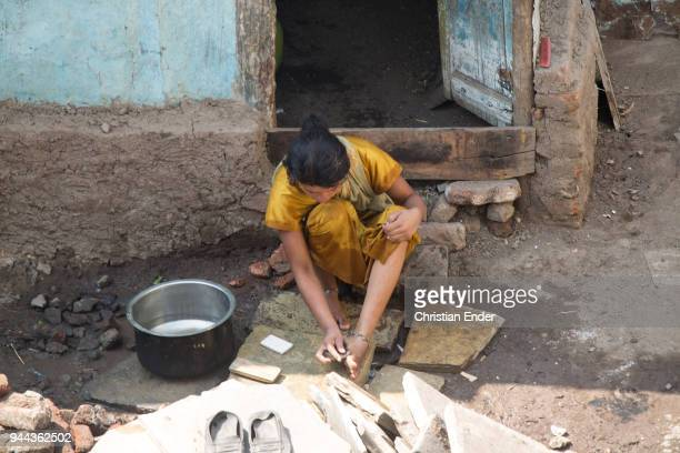 A woman in a yellow sari who is washing her feet with soap in front of a shack in a poor neighbourhood on March 28 2013 in Bijapur India Around 50000...