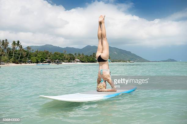 woman in a yoga headstand, stand up paddling (sup) board - beautiful beach babes stock photos and pictures