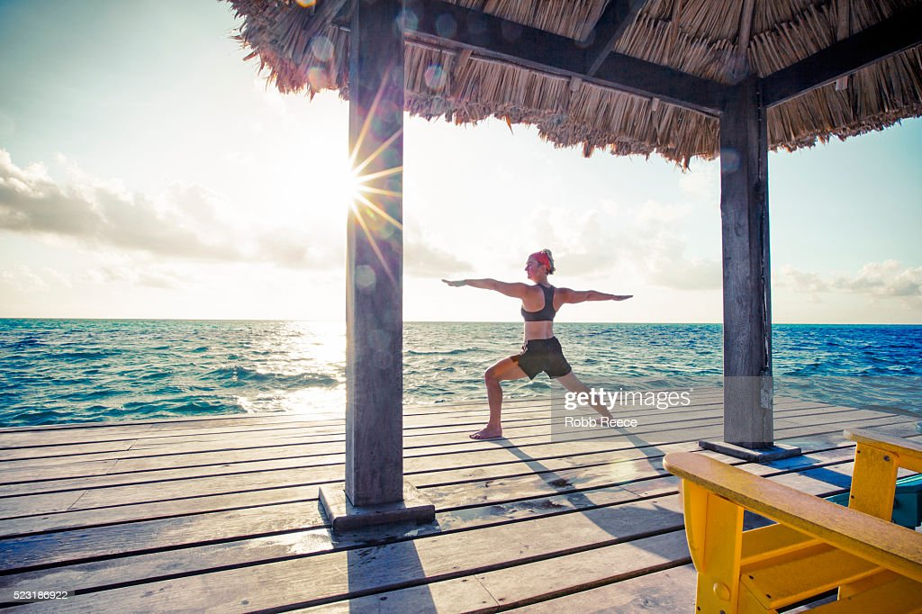 A woman in a yoga pose on a dock in Belize. : Stock Photo