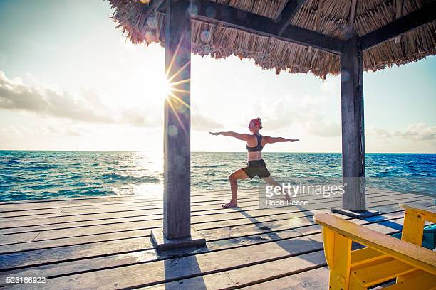a woman in a yoga pose on a dock in belize. - robb reece stockfoto's en -beelden