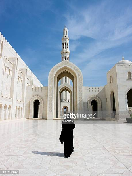 Woman in Abaya Cloak walking towards Archway of Grand Mosque