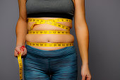 Woman in Active Wear With Squeezed Measuring Tape on a Gray Background