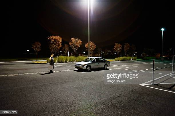 woman in alone in parking lot - car park stock pictures, royalty-free photos & images