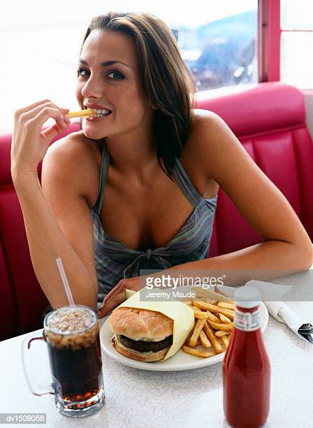 Woman in an American Cafe Eating Hamburger and Chips with a Glass of Cola