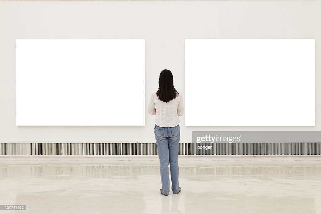 A Woman In An Art Gallery Looking At White Frames Stock Photo ...