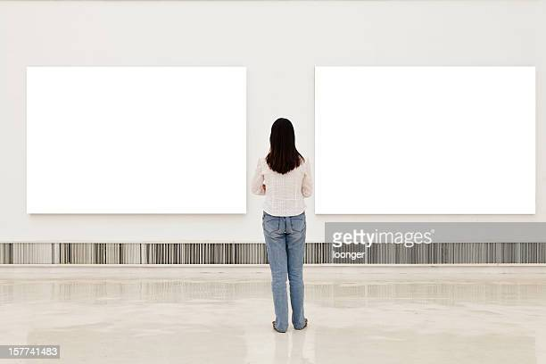A woman in an art gallery looking at white frames
